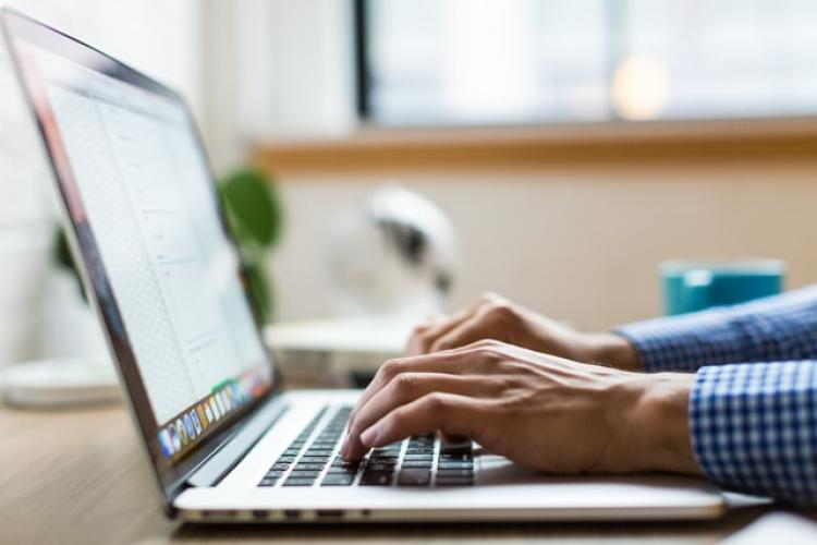 Photo of person typing at computer